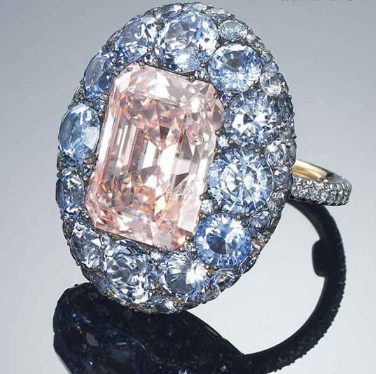 珠宝设计名师之作向来是香港佳士得珠宝拍卖不可缺少的一环,本系列的焦点之一是一枚由JAR打造的8.59克拉长方形彩粉红色VS2钻石及蓝宝石戒指。这个以巴黎为基地的美国珠宝品牌素以巧手工艺而闻名于世,品牌不仅设计非凡、工艺精湛,且所选用的宝石均非常稀有(拍品编号1828,估价:港币24,000,000-35,000,000/美元3,000,000-4,500,000)。   这颗色泽浓艳的粉红钻石以蓝宝石围绕,形成特别的对比,呈现出十八及十九世纪珠宝风格。Joel Arthur Rosenthal堪为全球